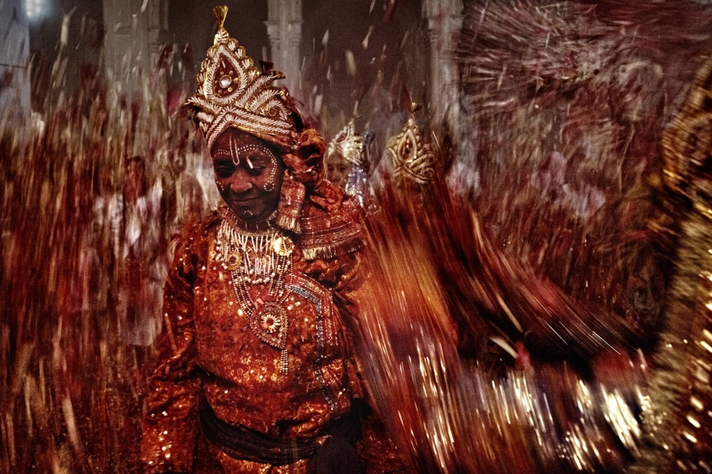 A widow dressed up as hindu goddess plays Holy with colour powders and flowers