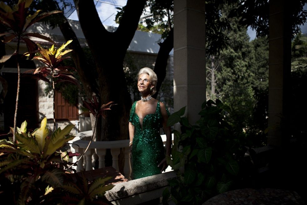 """JOUNIEH, LEBANON Regina Fenianos, President of the Debutantes Ball, in her garden in Jounieh. Mrs Fenianos created the Ball 16 years ago, being brought up in Brazil where Debutante Balls are the norm at 15, Fenianos' dream was to create one for her future daughter. However she had three boys, and so, she created the Ball for Lebanese girls to make """"their dream come true and become a princess for the night"""". To take part, it costs approximately $2,000."""