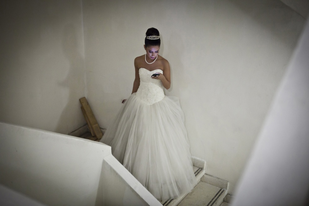 JOUNIEH, LEBANON Dima Arabi, the oldest Debutante participant, 24, checks her phone in the hallway backstage of the Debutante Ball.