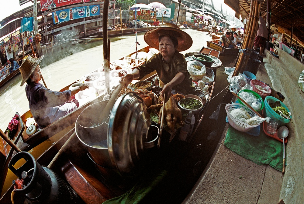 Women cooking in floating kitchens. Damnoen Saduak, floating market, Bangkok, Thailand.