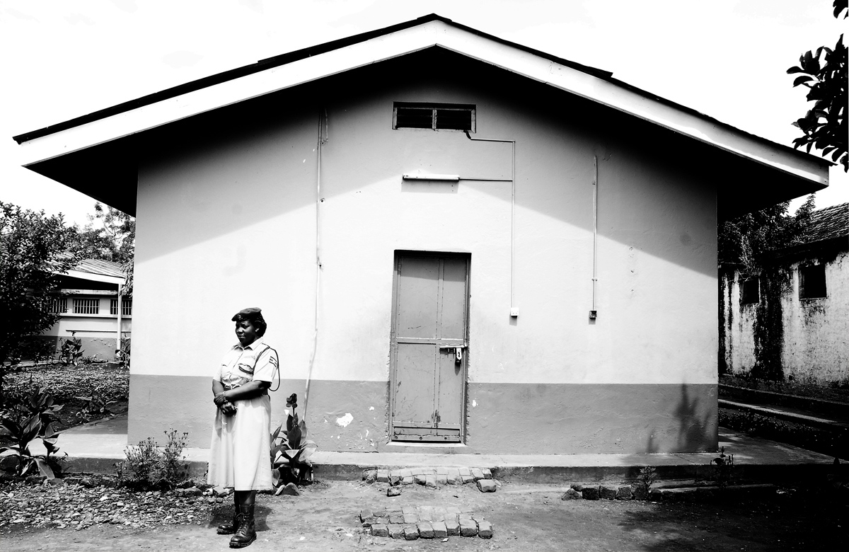 A PRISON OFFICER stands before the barracks that are temporarily housing the women prisoners at Gulu Prison. The women were moved there after the 150-year-old compound was found to be condemned. Renovations have yet to commence and are delayed in definitely said the Office in Charge. The women are held in the old prison that at one time held both women and men, but due to the increase in the male prisoner population UPS (Ugandan Prison Services) has constructed a newer compound for the men.