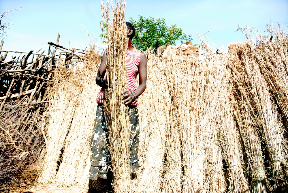A Karamojong woman organize dried grass she will use to construct the thatched homes of manyattas. Women in Uganda make up more than half the workforce, often taking on rigorous physical work like farming and construction in addition to being the primary caregiver to large families and commonly in spite of abject poverty and major health setbacks (disproportionately affected, they account for 57 percent of all adults living with HIV/AIDS in Uganda).