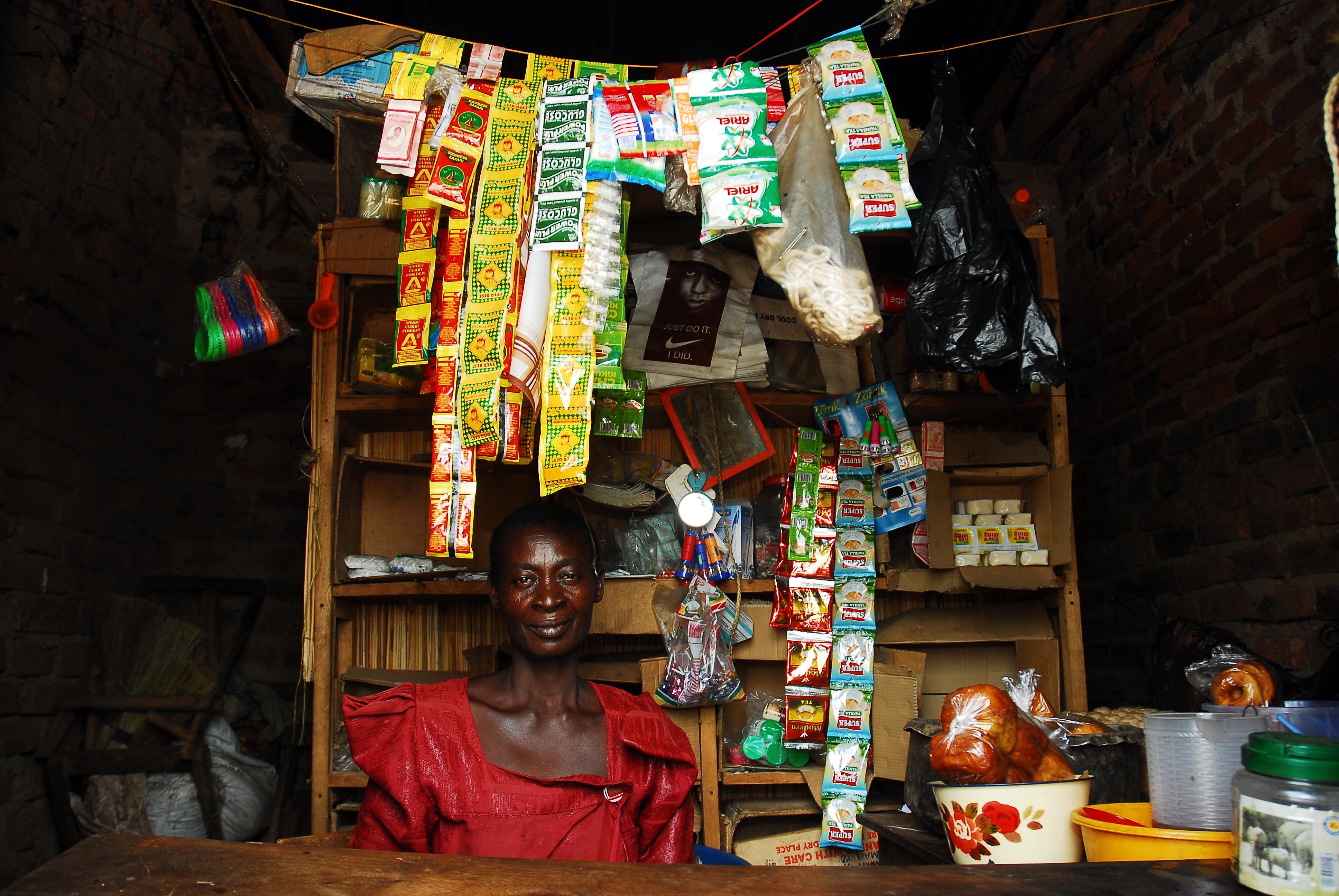 Donatella sits in her store outside Lugala town. The economic autonomy of women has been proven to further economic, social and health successes worldwide yet this is further thwarted due to customary laws which prohibit women from owning land or having assets making them instead more vulnerable to poverty, disease and domestic violence.