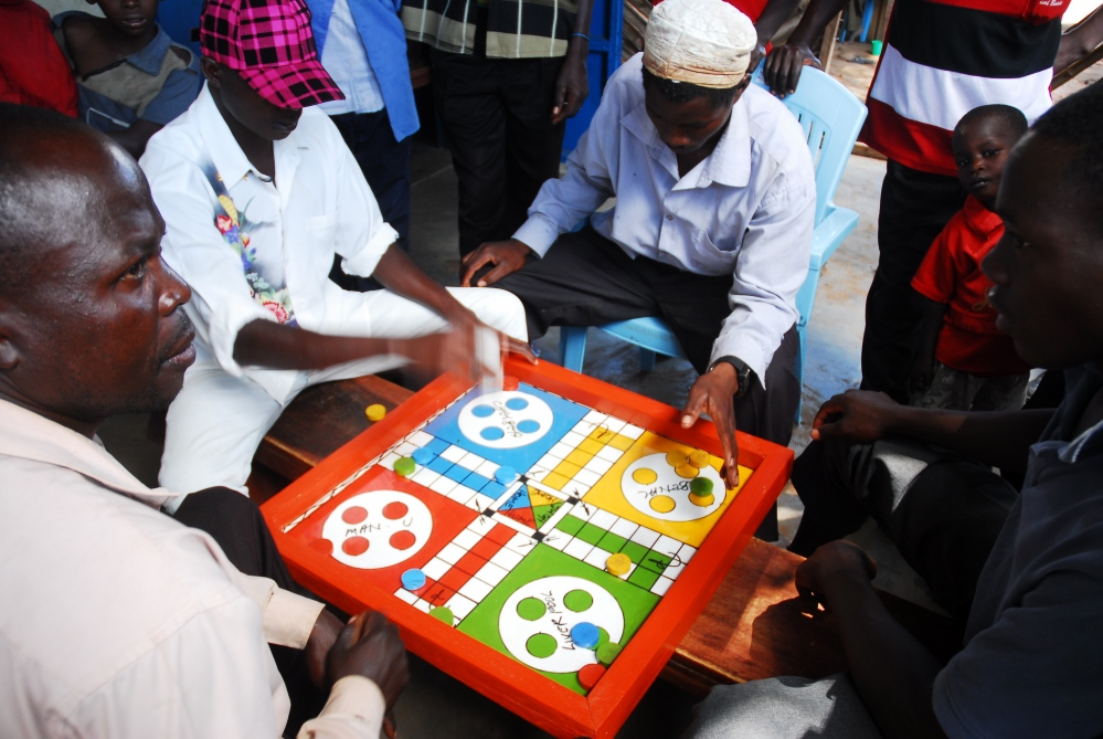 Fisherman at Lugala Knowledge Center play a game of Ludo between fishing trips.