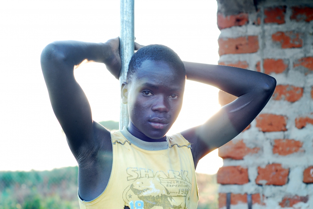 A teenage boy in repose at center for street children in Kotido. The home was later assessed for its child welfare and found to be acting as a business rather than a safe house - children were not in school, children with disabilities were without proper assistance and the children's status as orphaned or not were unclear.
