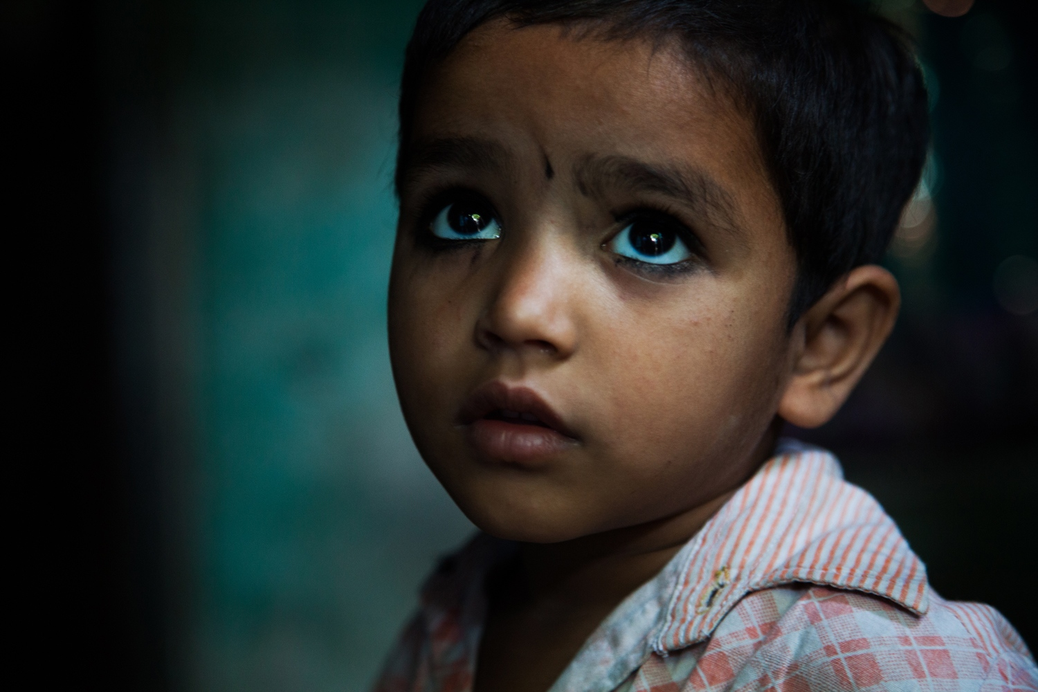 A child in a house in Moradabad, India, being visited by a vaccination team.