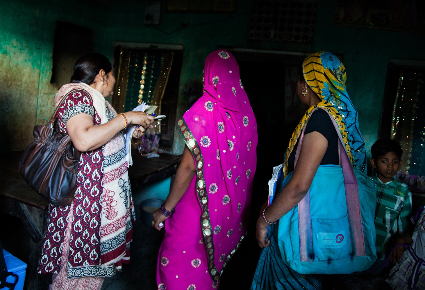 "A polio vaccination team in the village of Raftan Pur Kalam visits a house to vaccinate its children for polio. From left to right: the midwife, Bhaghirathi (prefers not to give last name); Poonam Kumari, 29, the ""asha"", and Nidhi Sharma, the CMC."