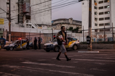 A crack addict walks by police officers in Cracolândia, São Paulo, Brazil.  With over one million users, Brazil has the dubious distinction of having the highest number of crack-cocaine users in the world. Cracolândia, in São Paulo, Brazil, is the symbolic epicenter of the battle against crack.