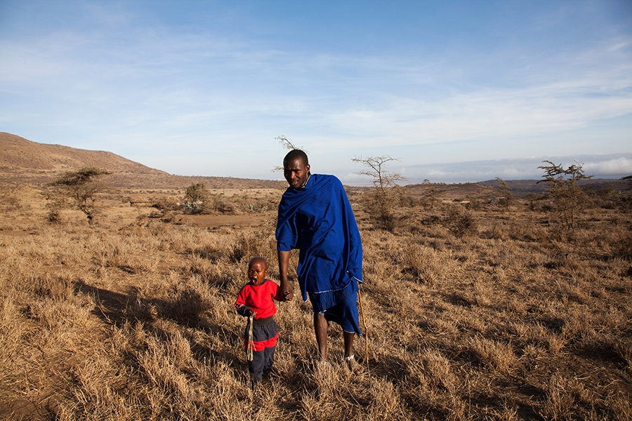 Paulo Papalay, 27, a Maasai warrior, with his 3-year-old son outside his home outside Mkuru, a sub-village in northern Tanzania.