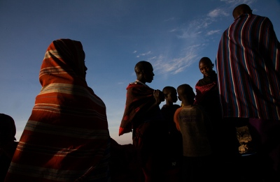 Women wait to fetch water at sunset in Mkuru, Tanzania.