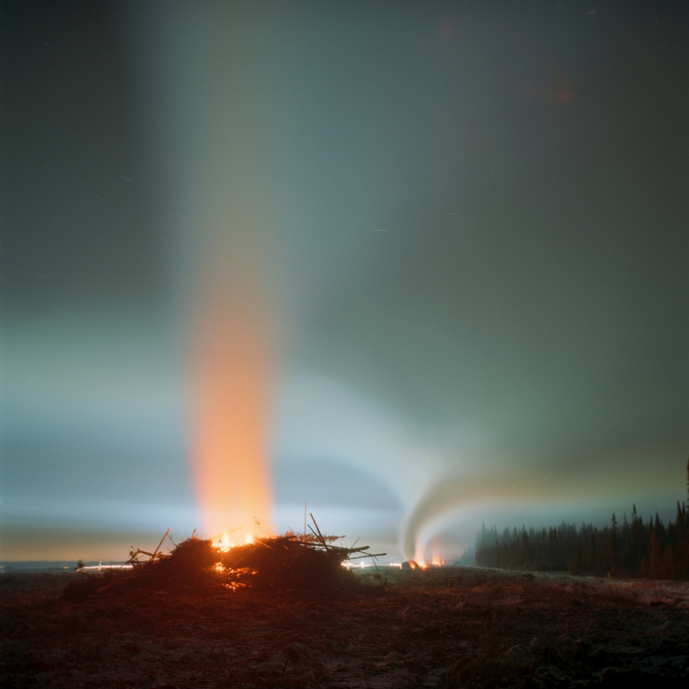 February 2012- Overburden, an industry term for the natural material that lies above an area of economic interest, is burned at night on the TOTAL Joslyn mine lease near Fort McKay First Nation, Alberta. Four months earlier the area was boreal forest with many trails used by the First Nations of Fort McKay. Companies from Fort McKay held many contracts with TOTAL, but since the drop in oil prices they have decided to withdraw their investment in the region.