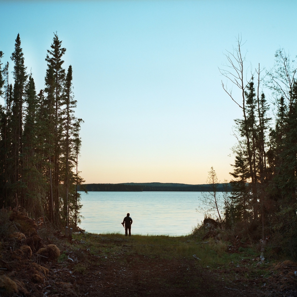 September 2013- Garnet Ahyasou stands by Buffalo lake on Fort McKay's Moose Lake reserve 50km west of Fort McKay First Nation, in Northern Alberta. Suncor Energy provides free flights to members of the band to their historic hunting grounds each summer to practice their traditional ways, but a new development called the Dover Project that will boarder Moose Lake and Buffalo Lake is threatening the health of the land and water.