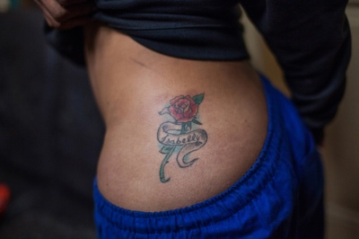 "Isabelly Santana, 23, a transgender prostitute part of an innovative harm reduction program called Bracos Abertos (Open Arms) in Cracolandia, Sao Paulo, became a shemale at 16. She got this tattoo to celebrate being able to call herself a woman. Isabelly is one of the many addict women who speak effusively about gender violence. Being transgender here is an extra layer of danger. ""If you live here, you cannot be afraid of dying. My dream is to leave Cracolandia. No one has dignity in this place""."