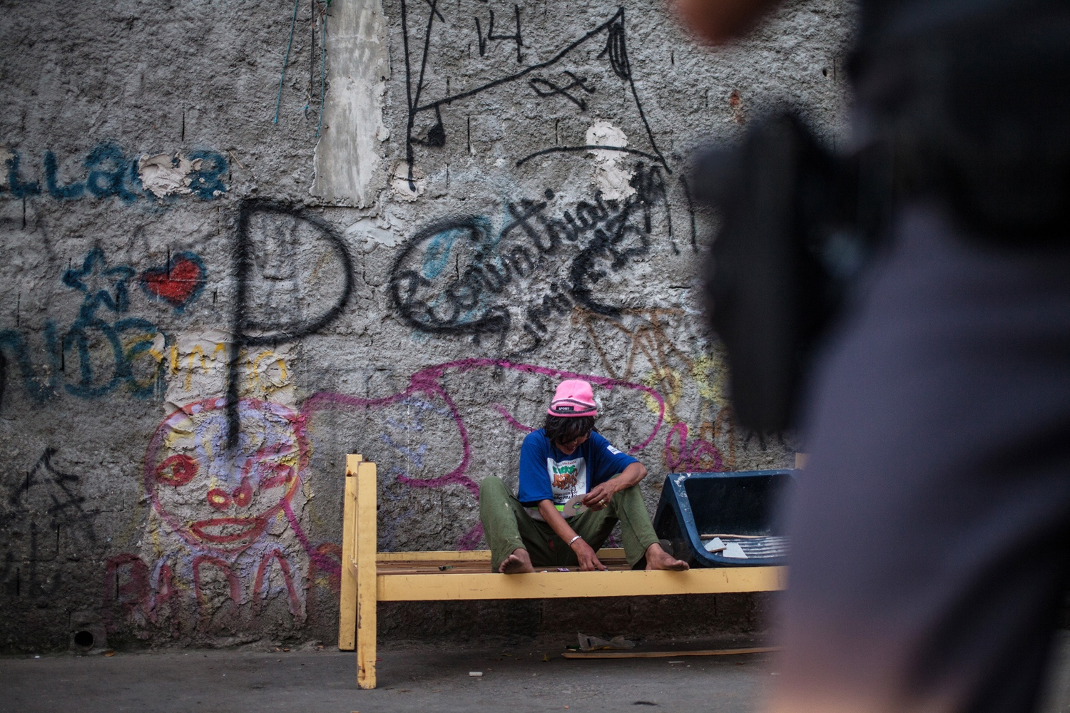 In January of 2014, São Paulo's government set up a harm reduction program called De Braços Abertos (Open Arms). It provides over 400 crack addicts with hotel rooms, janitorial jobs and food without requiring them to leave the drug. An addict who is part of the program sits on a bench while a police officer patrols the area. Most of the people arrested, usually outside the program area, are small-scale traffickers.