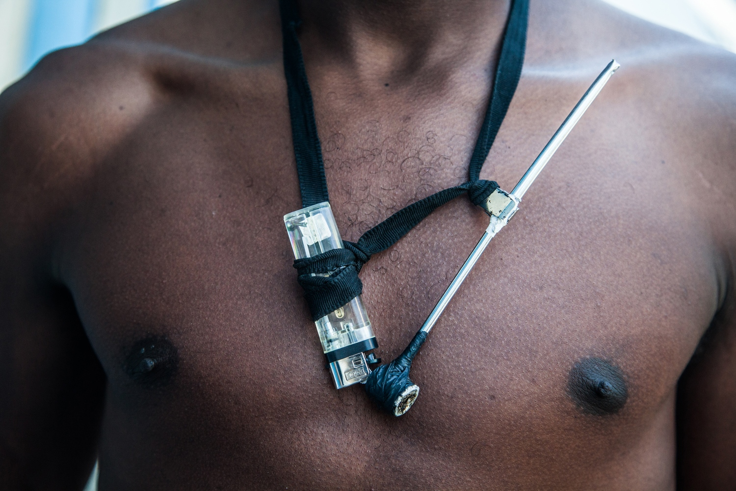 A crack addict stands with his crack pipe and lighter hung from his neck. Brazil has the dubious distinction of having the highest number of crack-cocaine users in the world, last estimated at one million people. Within Brazil, São Paulo's Cracolândia is highly symbolic of the country's drug epidemic.