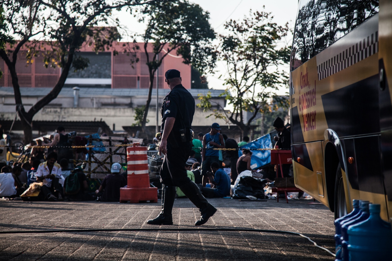 "An officer watches over the Fluxo, where users can openly consume. The writing on the van says 'It is possible to win the battle against crack'. Almost two hundred armed police are stationed nearby, on the lookout for traffickers and purse-snatchers. Until early 2014, most governmental actions regarding Cracôlandia residents have been coercive: involuntary hospitalization, violent police interventions, and forced dissipation techniques. This has recently changed, partially because crack is a hot-button issue in Brazil and voters demand the end of Cracôlandia. The police have unofficially declared crack users ""sick people"" instead of criminals, but buying and selling is illegal."