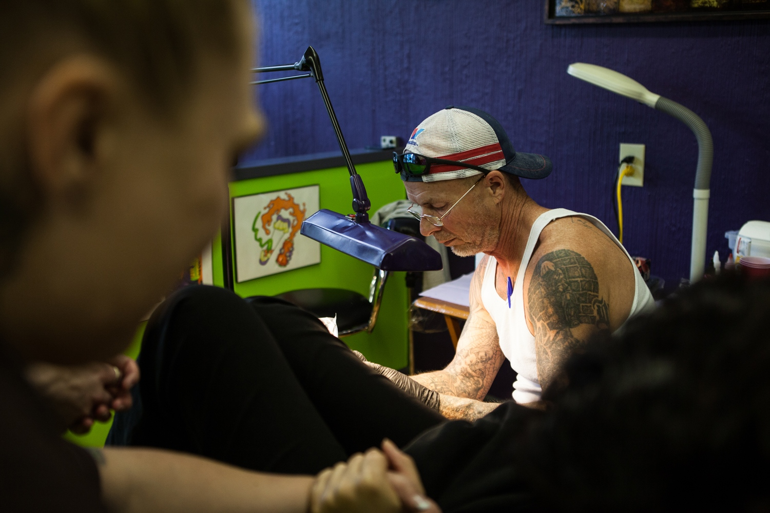 "Charles Waldo, a tattoo artist, tattoos Christina Brook's foot on a Saturday afternoon in a tattoo parlor in Lancaster, Ohio, USA. Waldo volunteers his time. The funds that Jennifer raises for the scholarships pay for renting the space, the materials and the ink.  ""Tattoo art has been around since the beginning of human history, and I find it deplorable that this is happening. When I think about trafficking, I never thought it was something that happened here in the United States. It gives me an appreciation that whatever trauma and turmoil I've had in my life doesn't even come close,"" Waldo said. ""But this gives me the opportunity to change their lives and help them move on""."