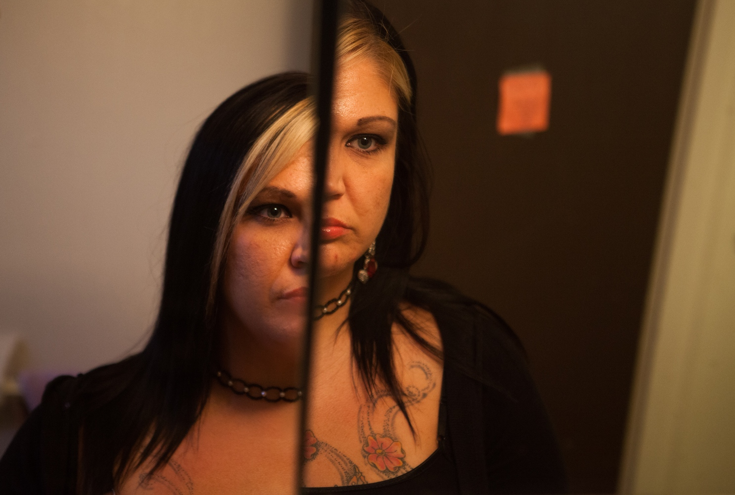 Melanie Dillon, 34, looks at herself in a mirror in the bathroom of an apartment provided by Amethyst, an organization that helps addicts and alcoholics, including sex trafficking survivors, get on their feet. Dillon has been in this apartment since January 2014.