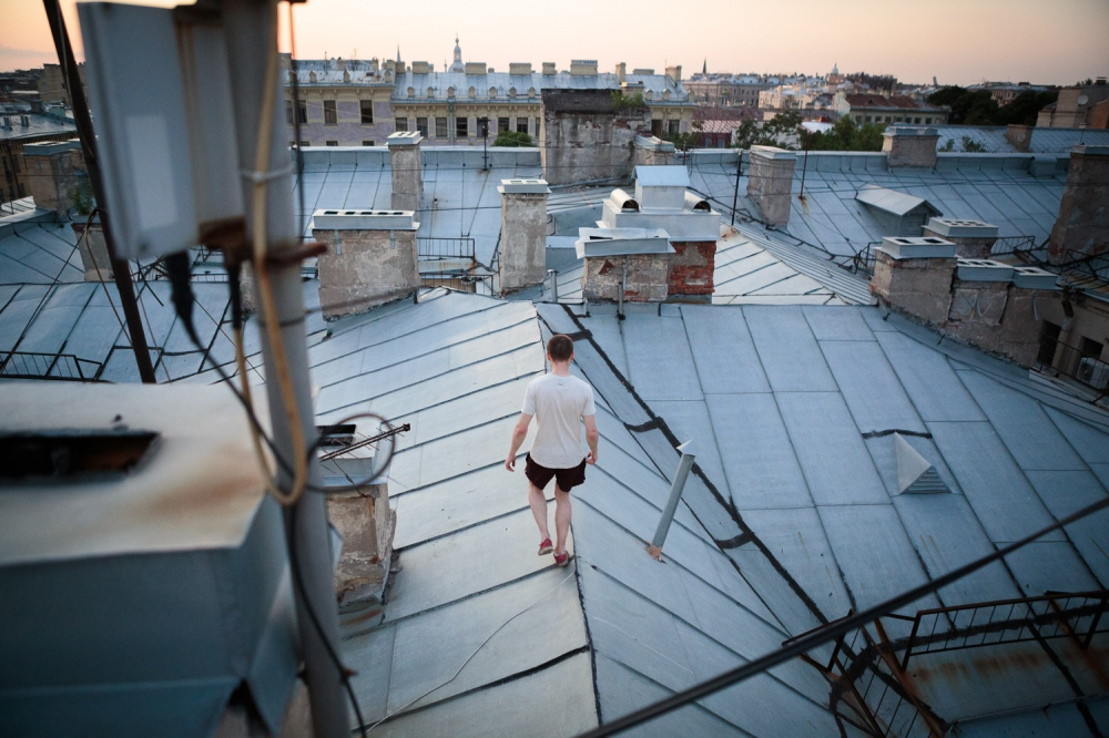 Alex Averianov, 23, climbs a rooftop in the center of the city during the summer's White Nights on July 14, 2013.