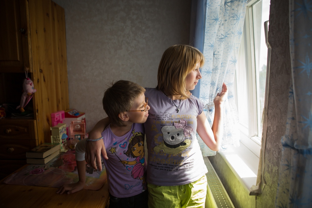 "Biological sisters Tamara, 9, and Antonina, 12, look out their bedroom window inside their home in the Pushkin S.O.S. Children's Village. One of the benefits for children entering an S.O.S. Children's village is that they are not separated from their biological siblings as they normally would be in a state facility or state foster care system in Russia. Antonina and Tamara were placed in the S.O.S village with ""mama"" Antonina two years ago."