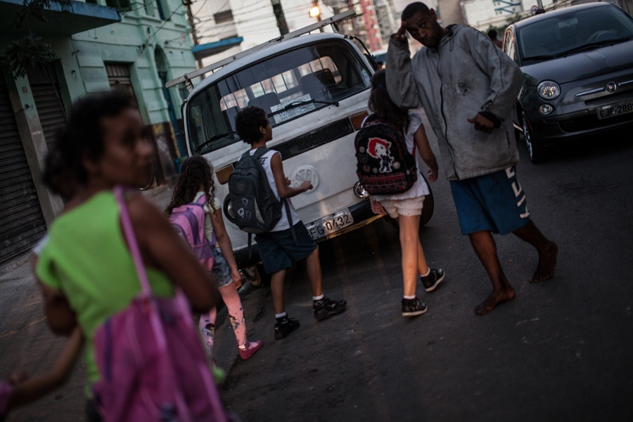 In the historic city center of São Paulo, Brazil, commuters and families walk through the Cracolândia district. Here, a woman with a baby and schoolchildren pass by a crack addict.