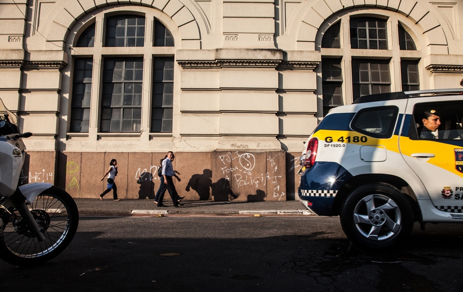 A police car patrols The Fluxo, in Cracolandia, Sao Paulo, while commuters walk by it. When officers have enough proof to arrest someone for dealing crack, they've learned the lesson to do it a few blocks away from The Fluxo to avoid heavy confrontations with the users.