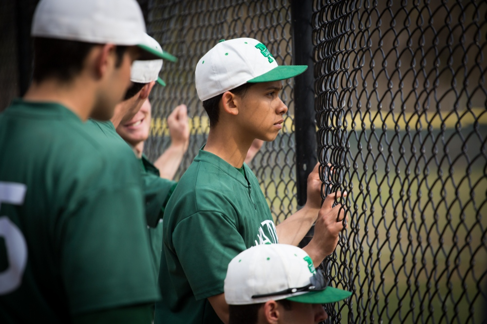 Tony Fernandez, #6, a sophomore originally from the Bronx, watches his teammates play from the dugout. The Manhattan College Jaspers play against the NYIT Bears on their home field at Van Cortlandt Park on Tuesday, April 22, 2014.