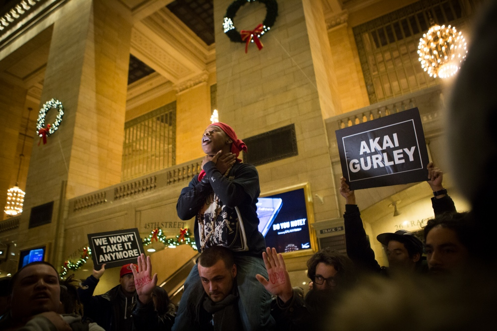 A man encourages fellow demonstrators to simulate choking themselves in Grand Central Station on Sunday, December 7, 2014. Demonstrators angry over a grand jury's decision not to indict a policeman in the death of an unarmed African-American man, Eric Garner, continue to show up in great numbers four days following the decision.