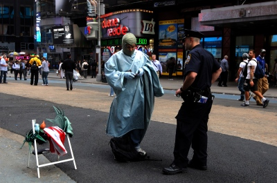New York, US, NYCPD member demands to see the documents of an Immigrant dressed up as Statue of Liberty, Times Square.