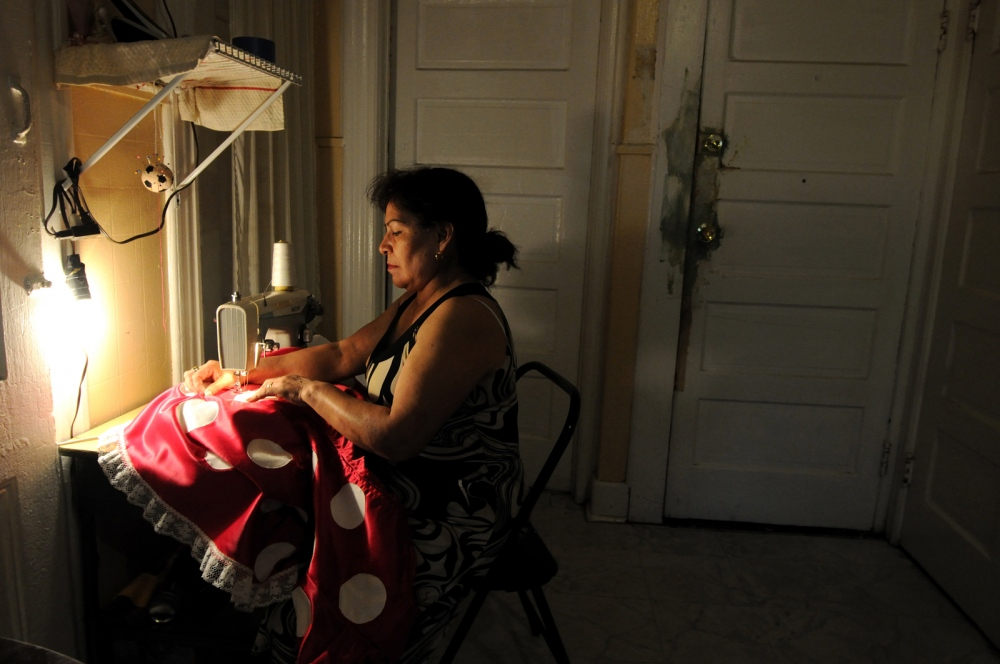 New York,US Doña Berta,55,from Mexico repairs her Minnie Mouse costume at her house.