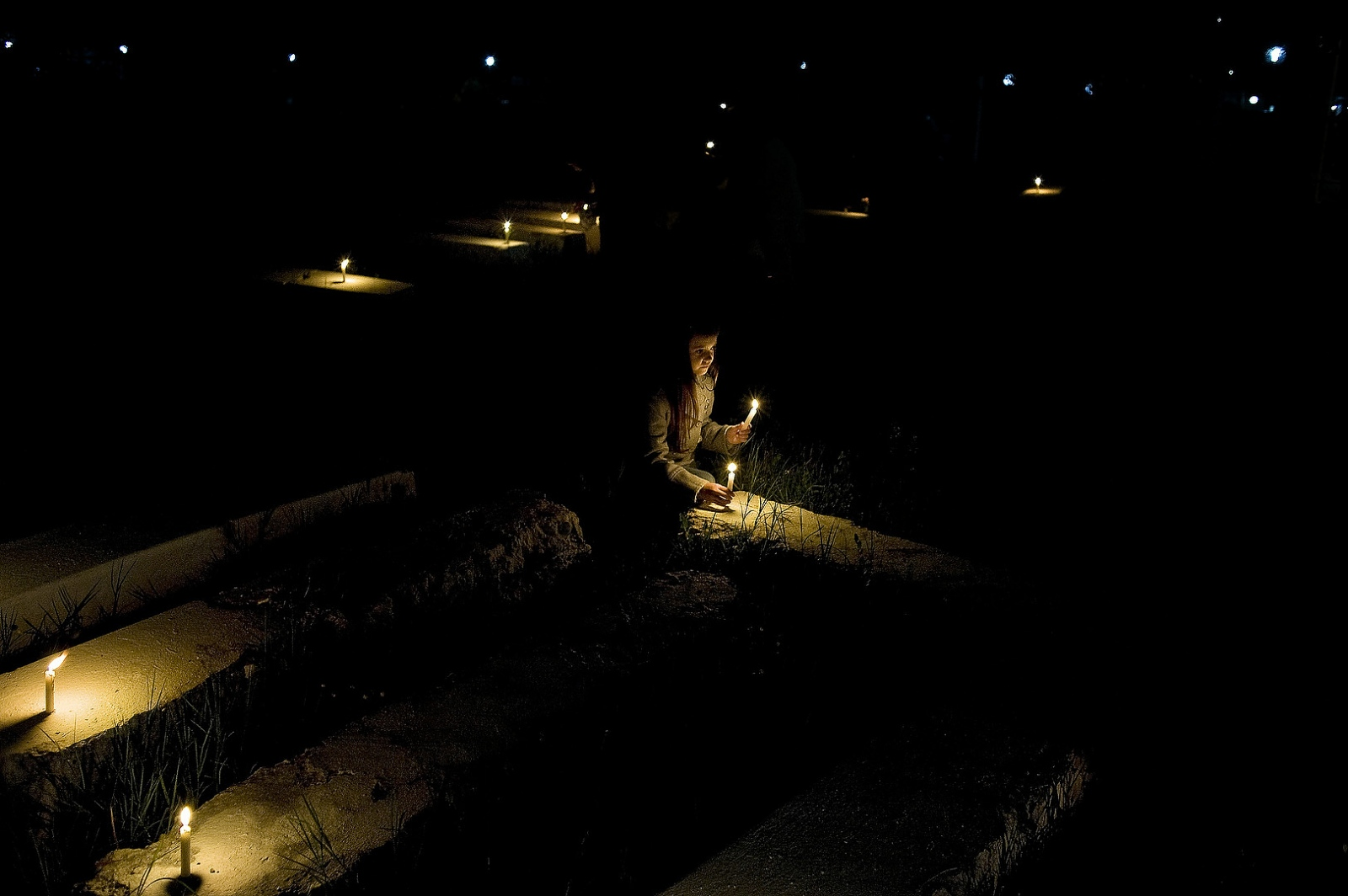 2010 - A young girl places candles on gravestones at the Jewish Cemetery of Ouazanne during the hilloulla or pilgrimage of Rabbi Amran Ben Diwan. During the yearly hilloulla hundreds of Jews return to his gravesite where they sleep for three days, pray and celebrate. His is one of the largest of many Hilloulot that take place all over the country.