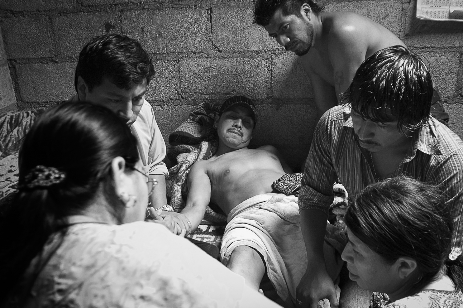 Berta Navichoc healing Pedro Mendoza, who is surrounded by his family