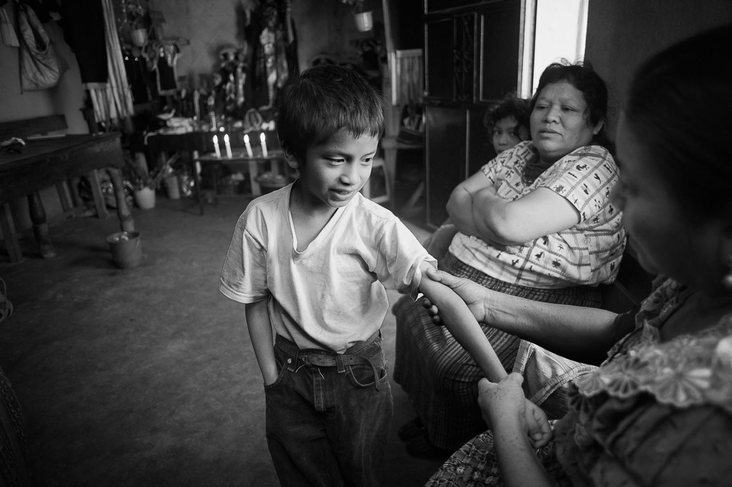 Berta Navichoc, bonesetter, treating a young boy with a broken arm