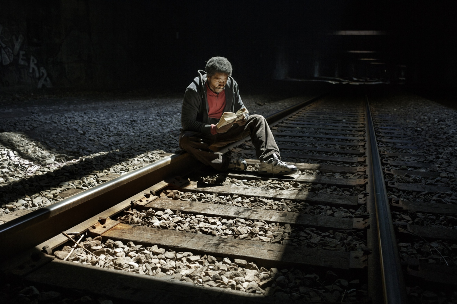 Light falls from the grates in the ceiling of the train tunnel. Chuck waits for his companion.