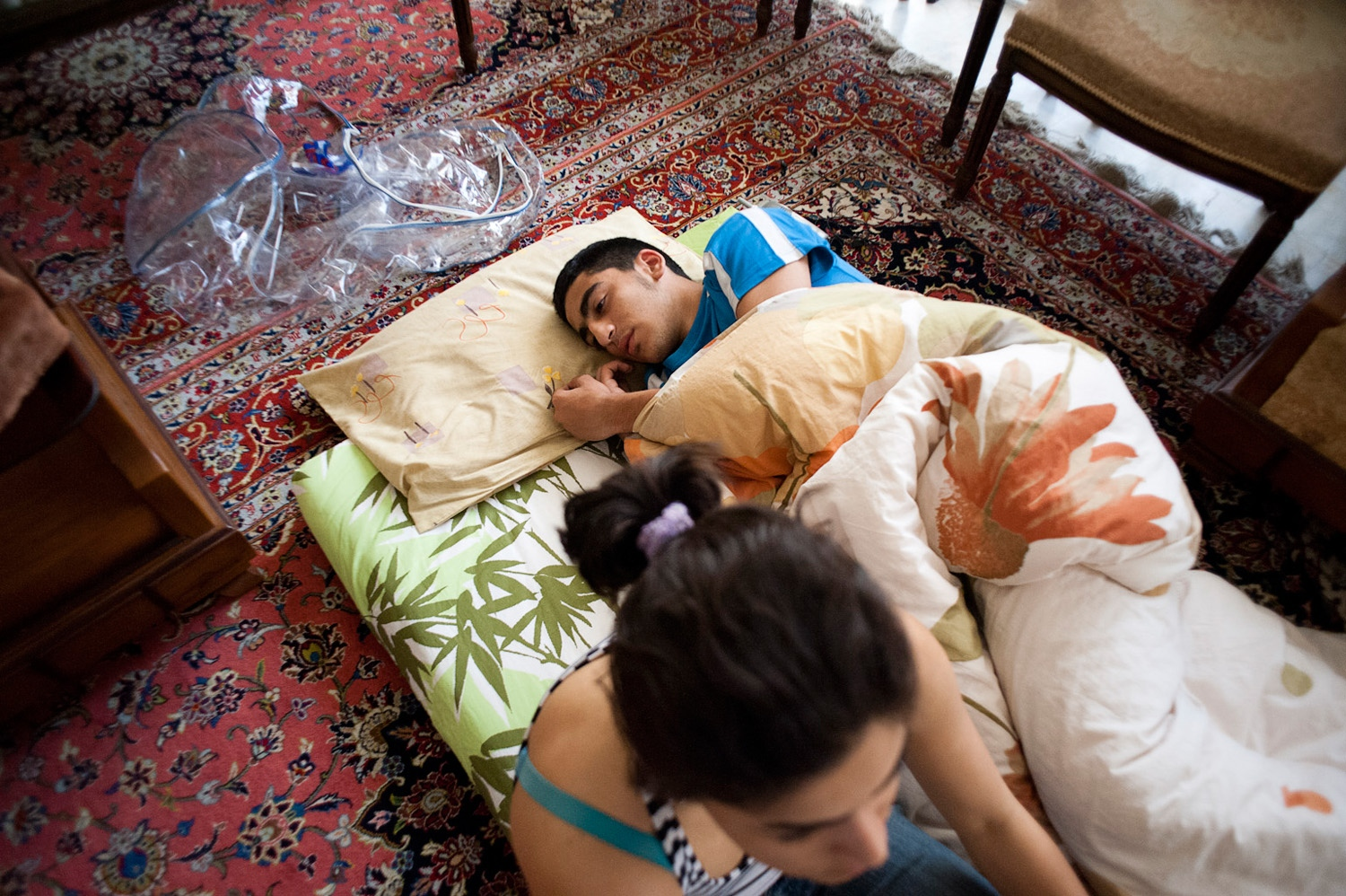 TEHRAN, IRAN -18/06/10 - Soroush, Parastou's brother, lies back on his mattress as Parastou and her mom continue to chat about her move.