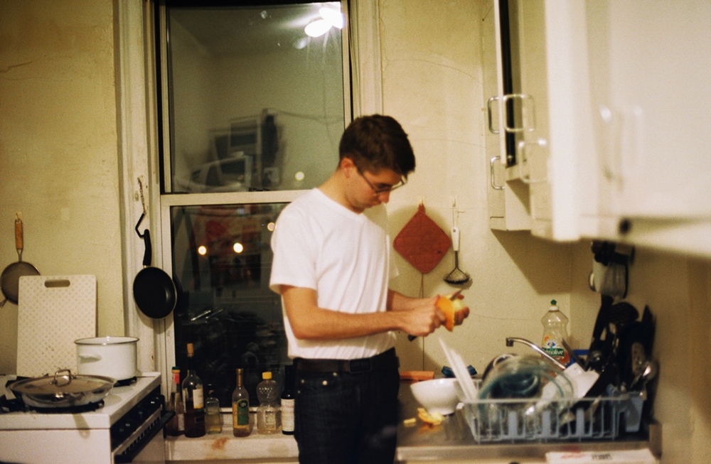 Denis peeling oranges in the kitchen, Brooklyn, NY
