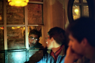 Denis reflected in a bar window, New York, NY