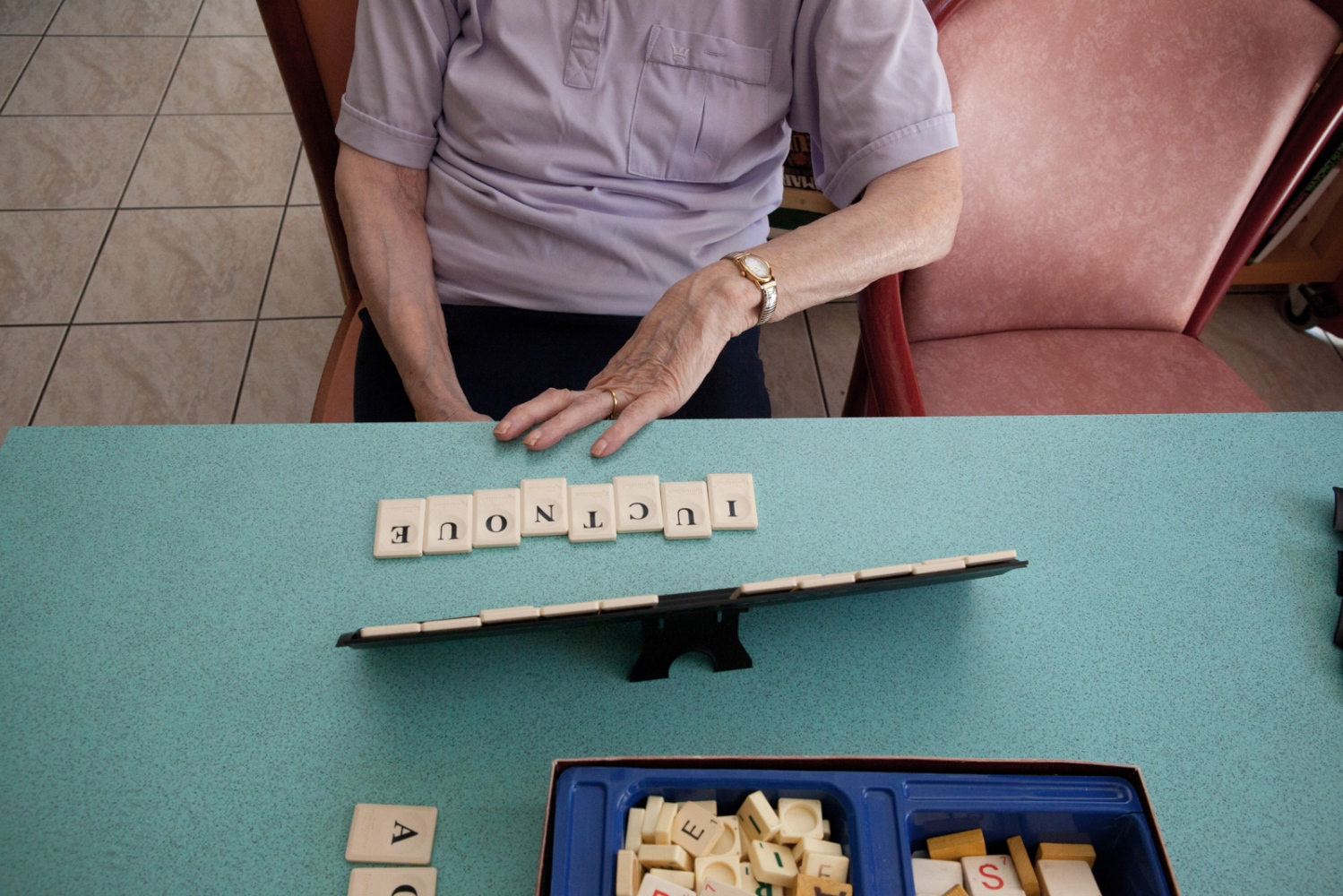 A lady suffering from Alzheimer tries with difficulty to play a Scrabble game. Daily life at Enclos Saint Césaire, Arles, France, 2011