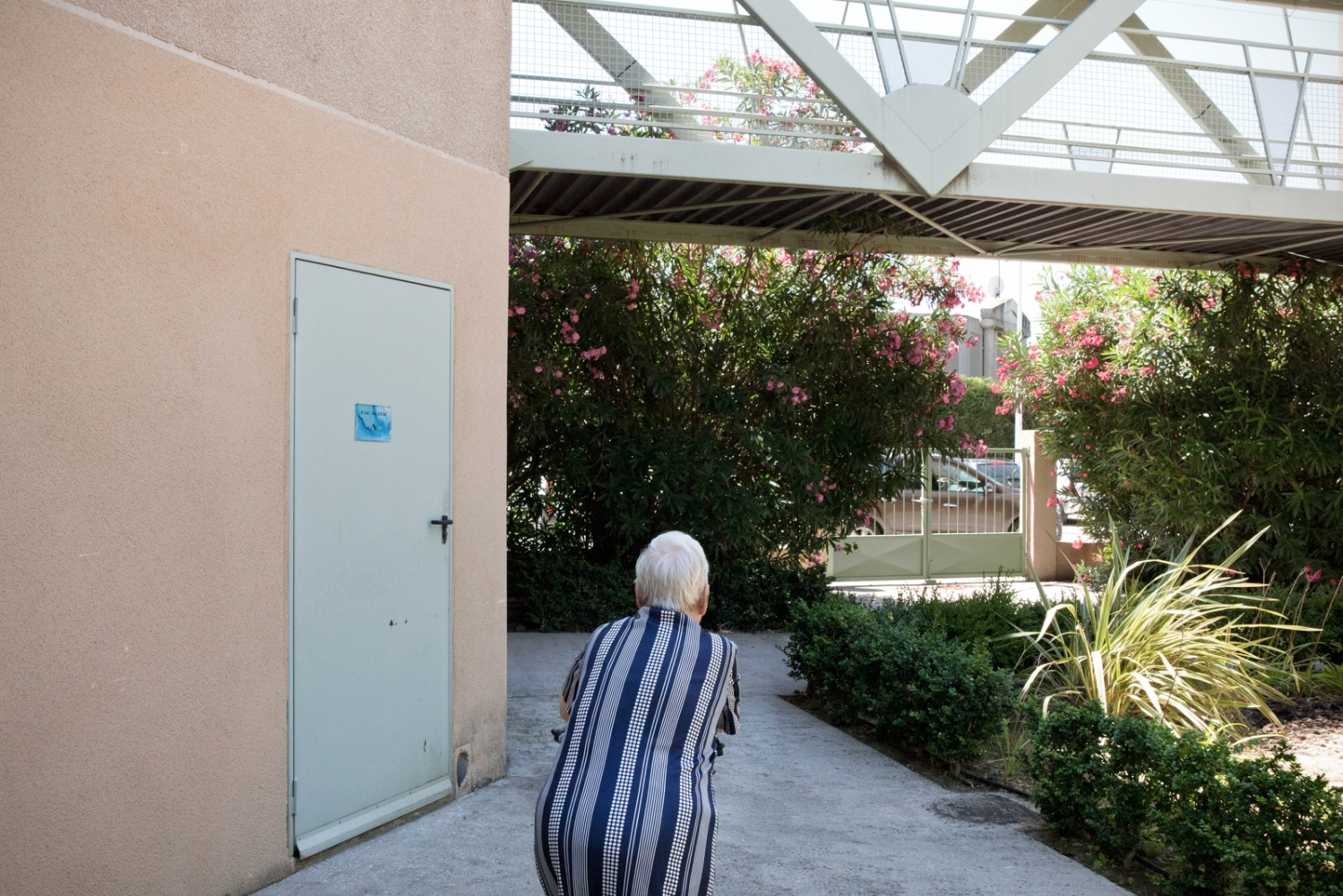 A lady walks in the internal garden of Enclos Saint Césaire. Arles, France, 2011