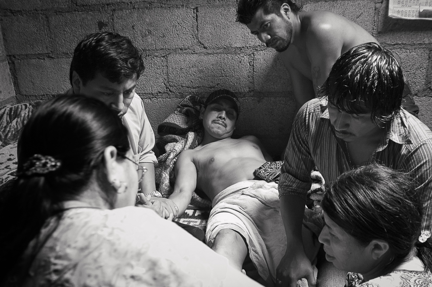 Berta Navichoc setting Pedro Pablo Mendoza's broken ankle after a work related accident. Pedro is surrounded by his family.