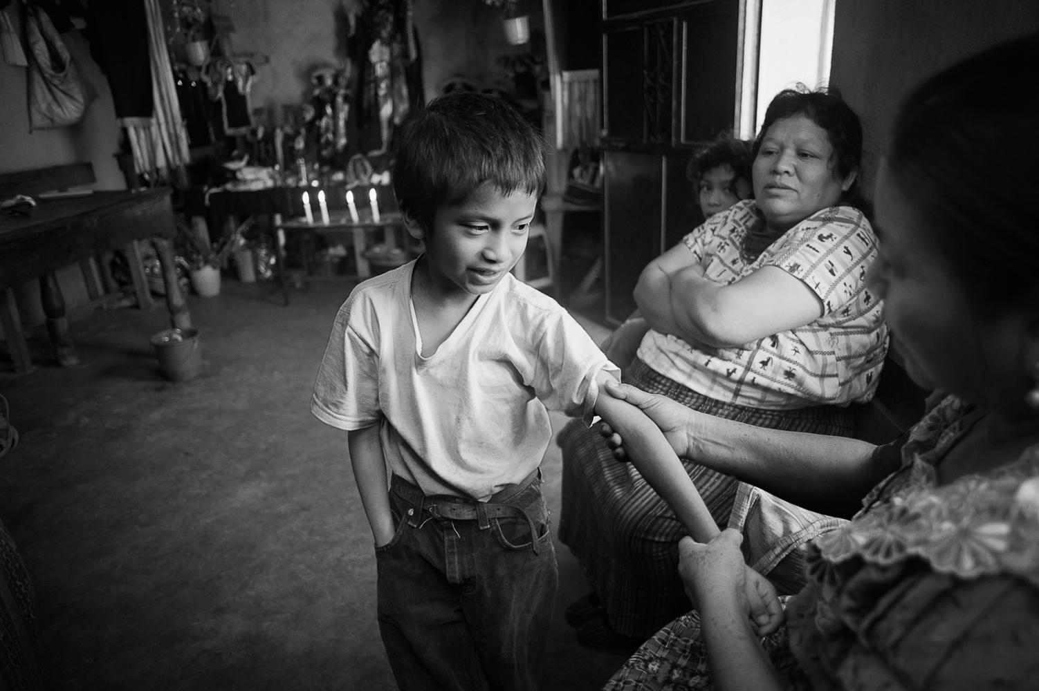 Berta Navichoc, bonesetter, treating Pedro Sicay Mendoza's broken arm, Santiago Atitlán.