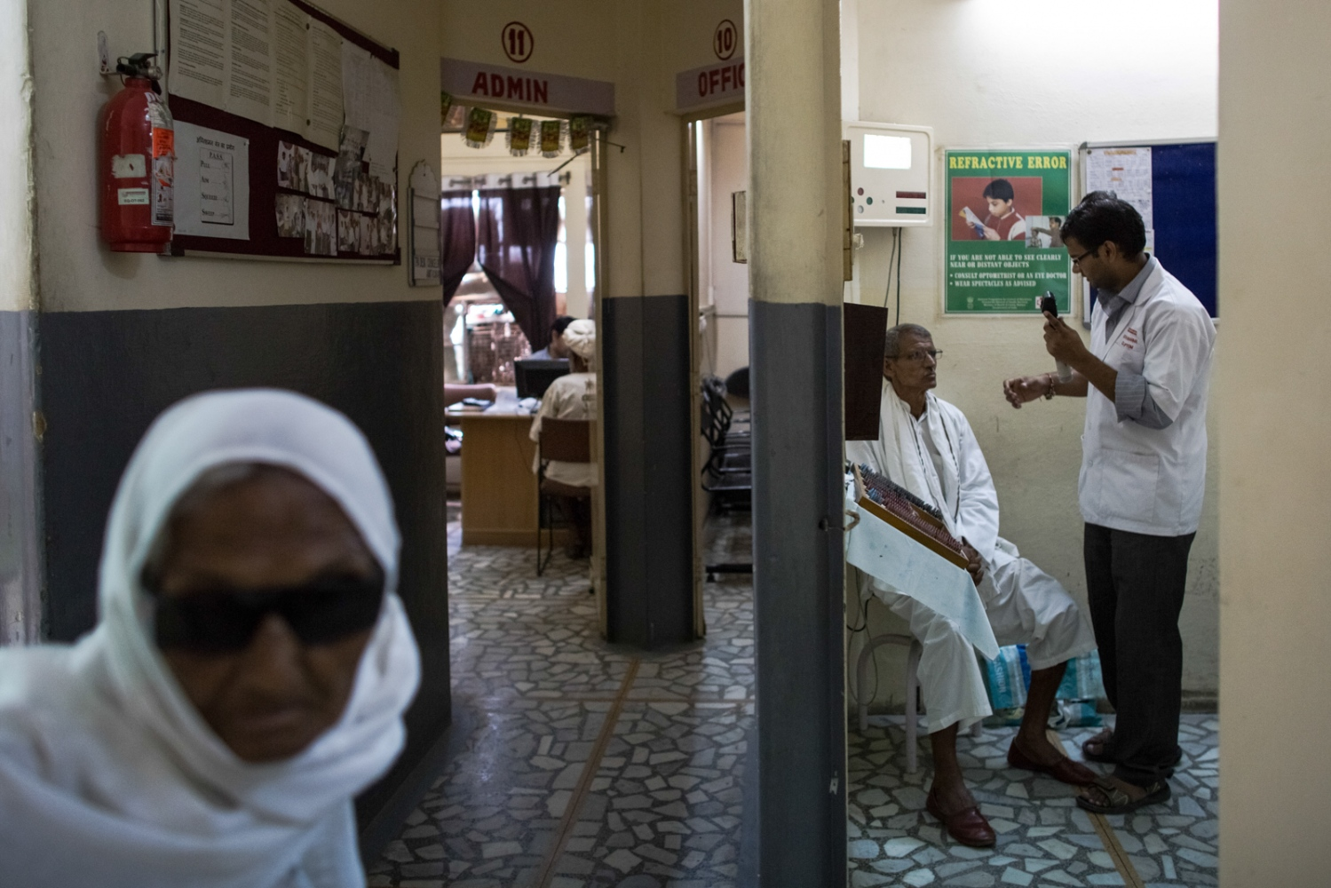 Indian patient walks past an examination room as another undergoes an eye test at the Dr Shroff Charity Eye Hospital in Alwar in the state of Rajasthan on August 28, 2014.