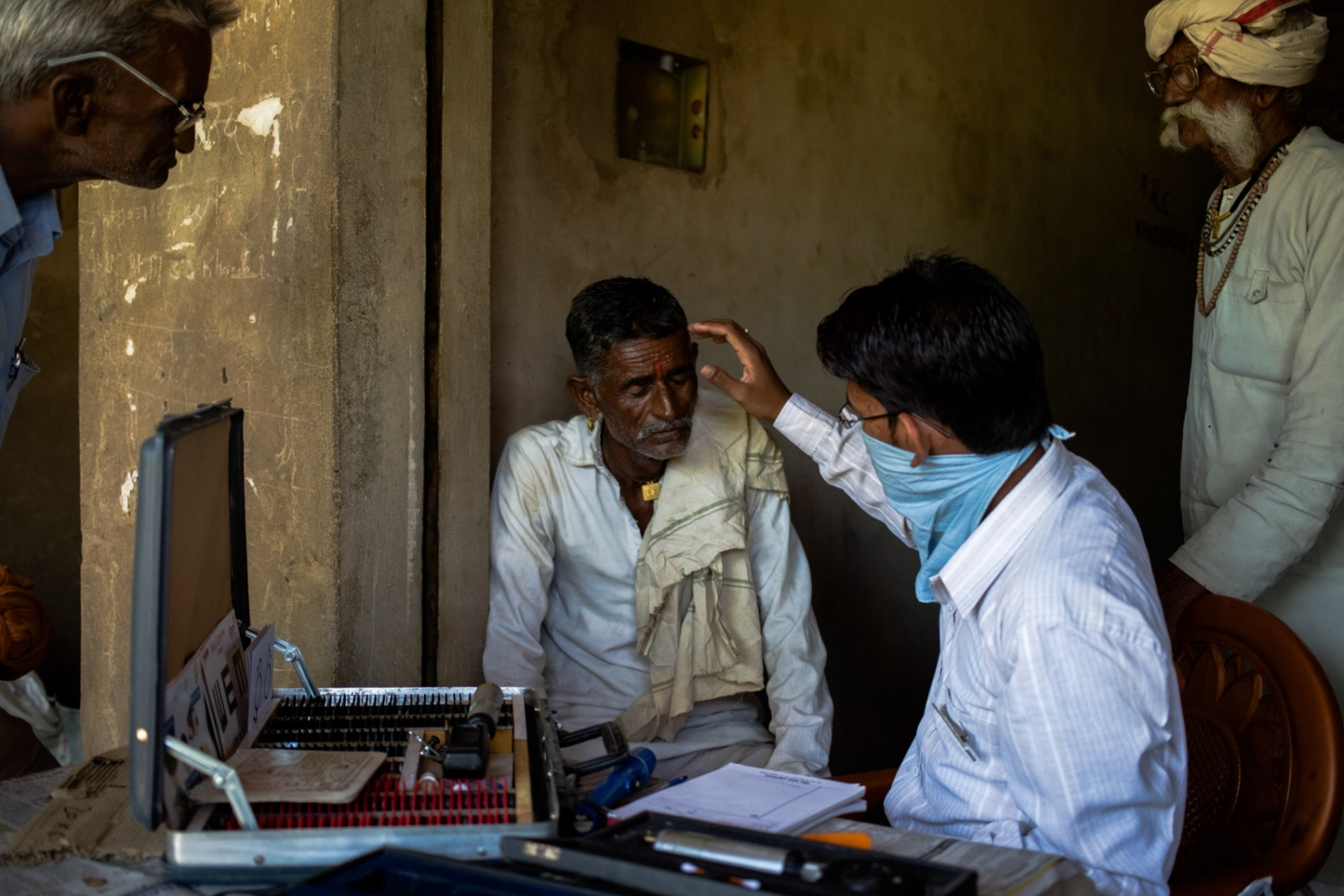Indian eye spcialist Dindyal Pirjapat (2R), 25, carries out an examination on villager Saidu Ram (C), 52, before referring him for a cornea consultation, as patient Bhuru Shay (R), 68, waits to be seen at a vision field camp run by the eye hospital in Nagledi village, Kusalgad, in Rajasthan's Alwar district on September 26, 2014.