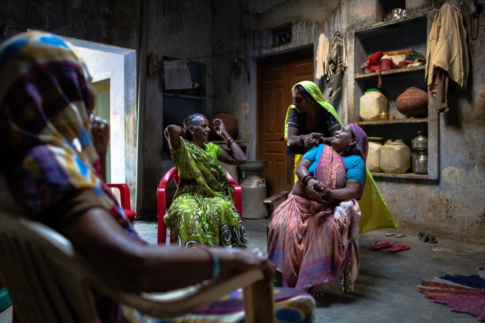 Indian patient Chameli (R), 50, who goes by one name and who has has successful cataract surgery on her left eye and is waiting for the same procedure for her right eye, talks with neighbours at her home in Malakhera village, some 30 kms from Alwar in the state of Rajasthan on September 26, 2014.