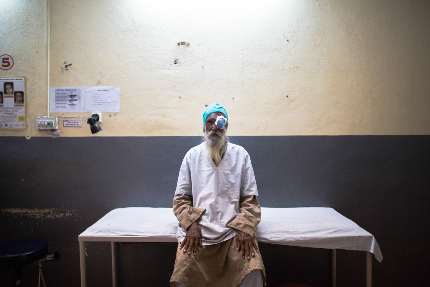 Indian cataract patient Balaji sits on an examination table after undergoing surgery at the Dr Shroff Charity Eye Hospital in Alwar in the state of Rajasthan on August 28, 2014.