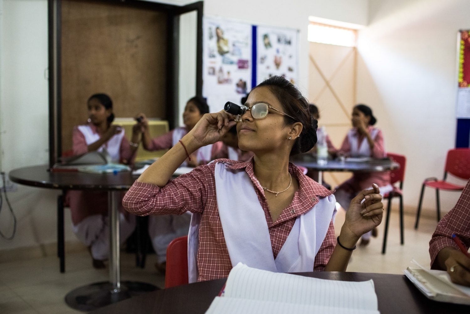 An Indian student uses a vision aid and glasses to simulate low vision as she takes part in a lesson during the Dr Shroff Charity Eye Hospital Certified Ophthalmic Personnel (COP) training programme in New Delhi on September 30, 3014.