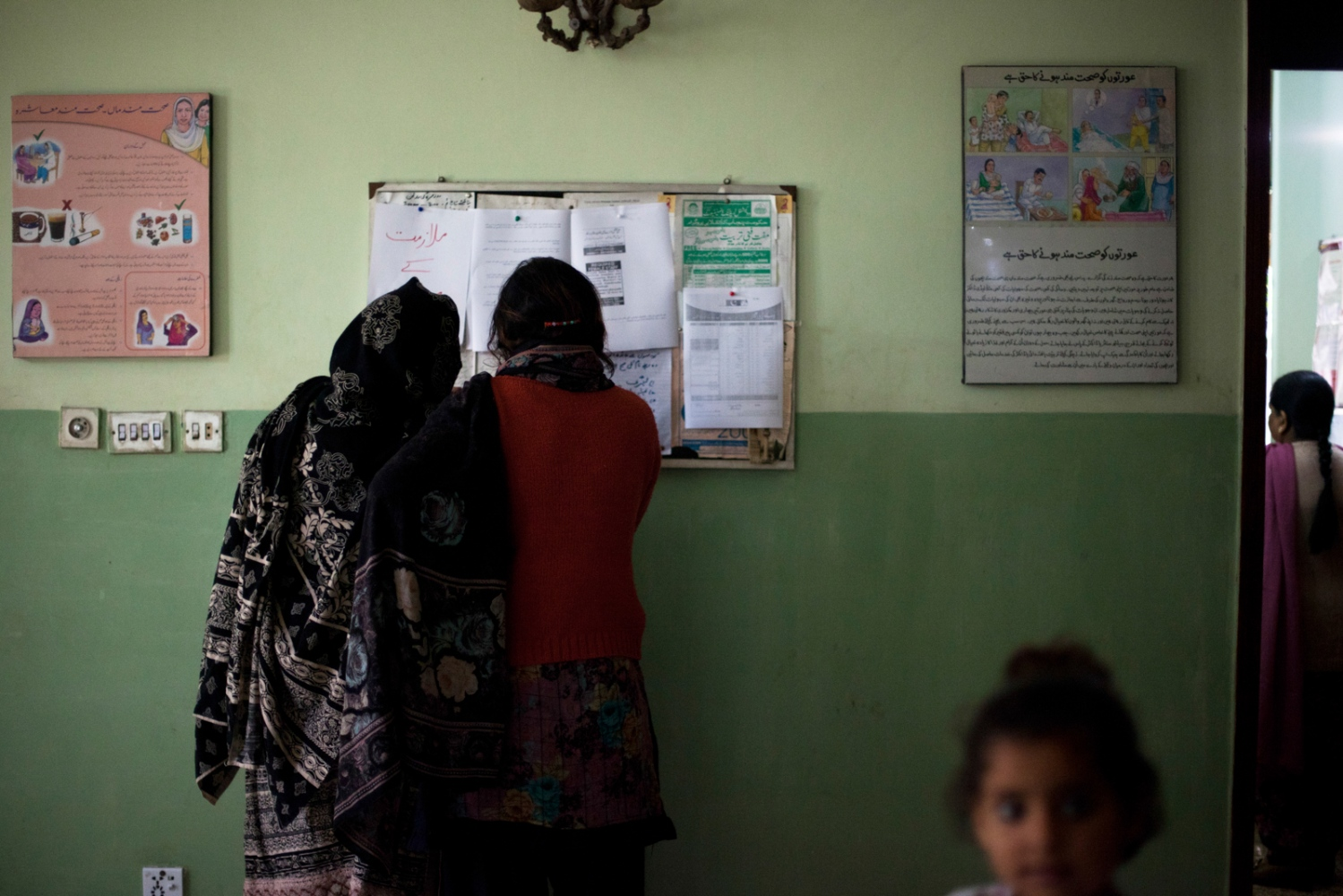 Pakistani residents look at a notice board advertising jobs at the Dastak women's shelter in Lahore on February 20, 2013.