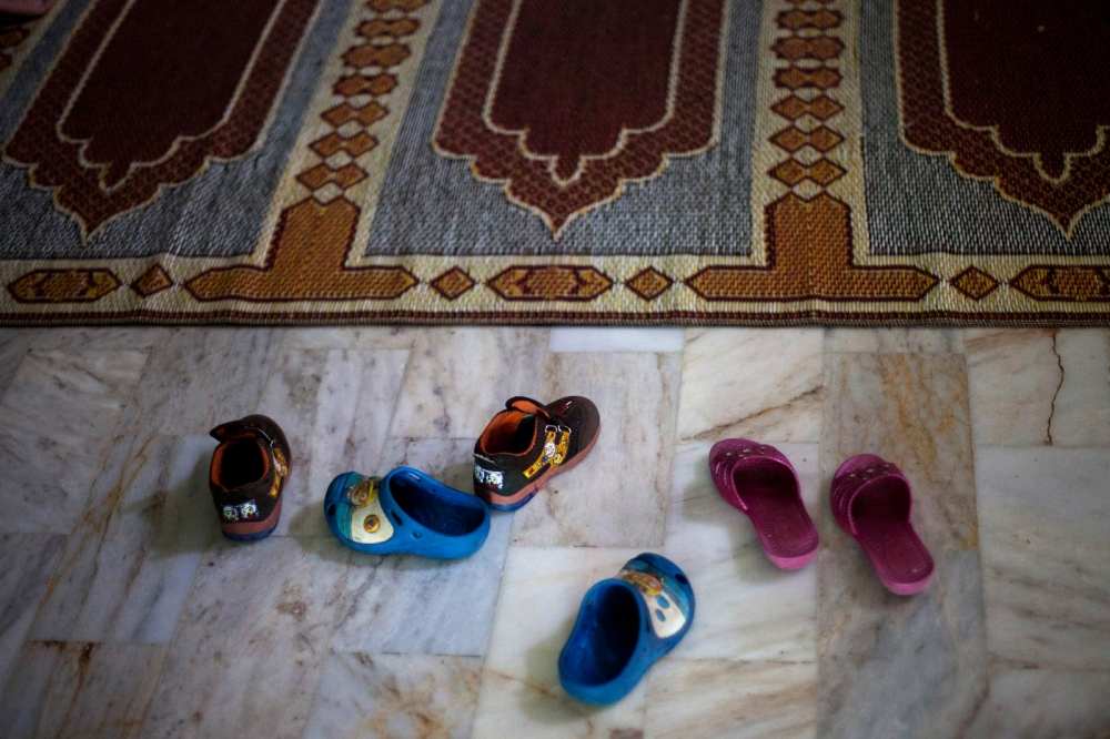 Shoes belonging to Pakistani children and shelter residents lie beside a prayer matat the Dastak women's shelter in Lahore on February 20, 2013.