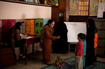 Pakistani house manager Akhtar Malik sings a nursery rhyme to children in the schoolroom at the Dastak women's shelter in Lahore on February 22, 2013.