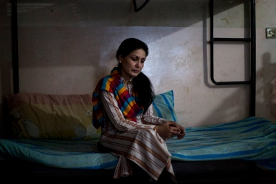 Pakistani Dastak resident Saira, 43, sits in a bedroom shared by other residents at the Dastak women's shelter in Lahore on March 1, 2013.